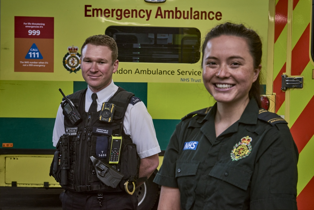 A police officer and LAS paramedic standing in front of an ambulance.
