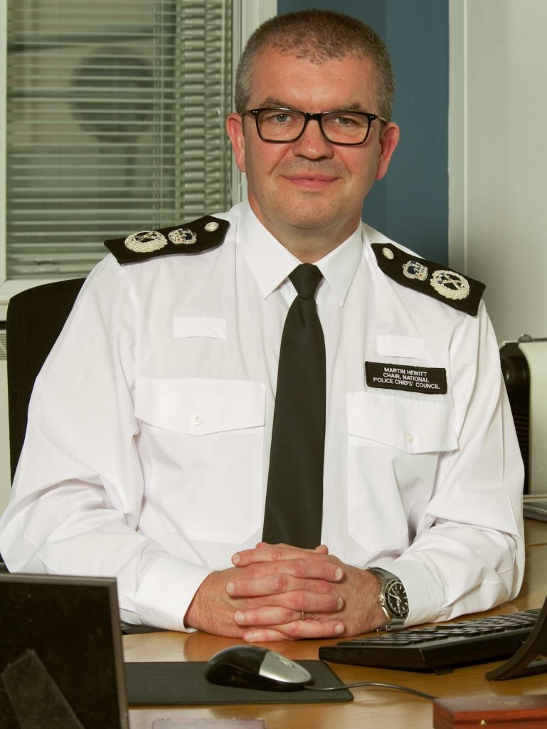 A picture of Martin Hewitt sitting at a desk, smiling.