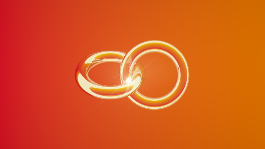 Two golden rings connected, background is orange